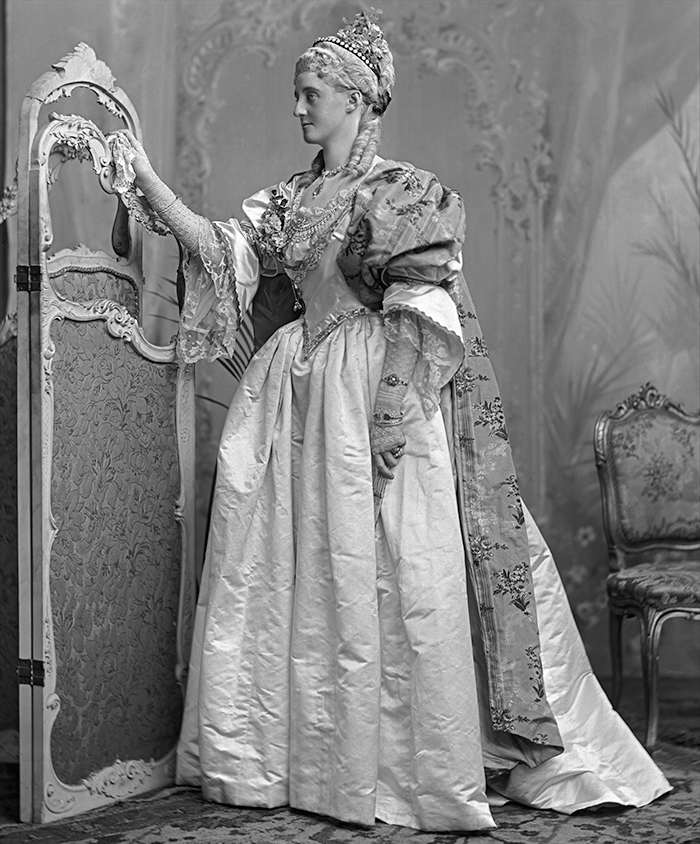 """...The long pointed bodice and full skirt were in rich ivory satin; the bodice and quaint bell sleeves outlined in old Louis XV embroidery, in the finest gold sequins, and bullion thread interspersed with small rose tinsel flowers. The berthe, in fine Brussels lace was sewn with old diamond ornaments. A lovely old scarf, in real Rose du Barry brocade, was suspended with old diamond buckles from the right shoulders, and was carried gracefully draped over the left arm, hanging in a long hem on to the skirt; a small cluster of roses fastened the lace at one side of the bodice. The hair was worn powdered, and rather low, in the style of that period, with a small bunch of the same Pompadour roses as on the bodice. Long lace mittens were worn instead of gloves."" (The Queen, 10 July 1897, p 76b)."
